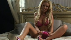 Blonde in lingerie stuffs herself with a dildo for the cameras