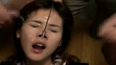 Pretty Japanese girl has a bunch of horny guys unloading on her face