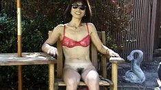 Mature Asian broad in a red bra plays with a dildo out in the open