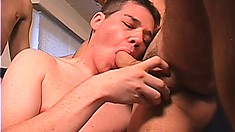 Cute young twink has his lips and hands taking care of two hard cocks