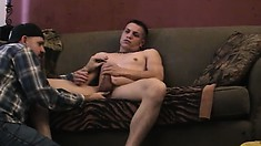 Young muscled guy lies on the couch and a horny dude sucks his big cock
