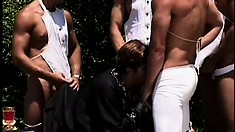 Handsome slaves service their master with an outdoors gay orgy